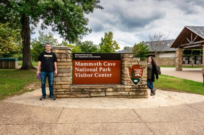 Us with the sign at Mammoth Cave National Park Visitor Center in Kentucky