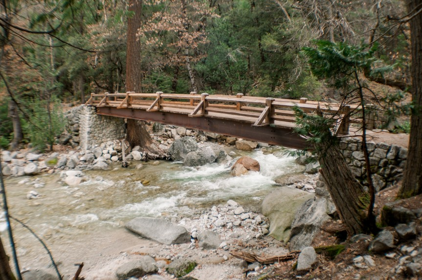 A Bridge near Mirror Lake in Yosemite National Park in California in the United States.  A bridge with slow flowing water underneath it.  The water is clear and running from higher up on the mountains.