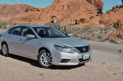 Posing with our rental car during a rental car road trip to Valley of Fire State Park in Nevada